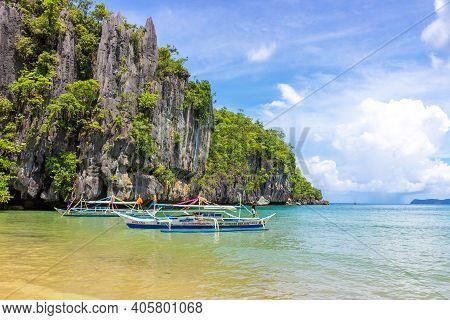 Puerto Princesa, Palawan, Philippines - September 26, 2018: Filipino Boats In Azure Lagoon Against R