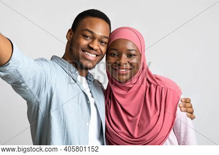 Selfie Of Smiling African American Embracing Couple On Grey Studio Background. Happy Lovers African