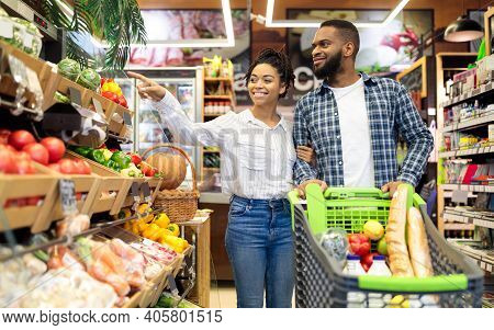 Black Family On Grocery Shopping In Supermarket. Happy African Couple Buying Organic Vegetabels And