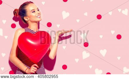 Valentine Beauty girl with red heart shaped air balloon pointing hand. Beautiful Happy Young woman presenting products. Holiday party, birthday. Love concept. Valentines's Day celebrating