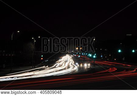 Long Exposure Of Red And White Car Light Trails On Highway At Night, Turning Curved At A Bend In The