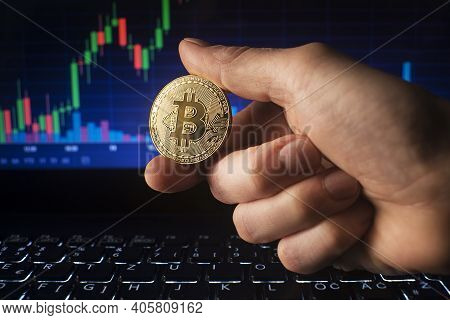 Business Men Holding Golden Bitcoin On Computer Trading Chart Background. Bitcoin As Most Important