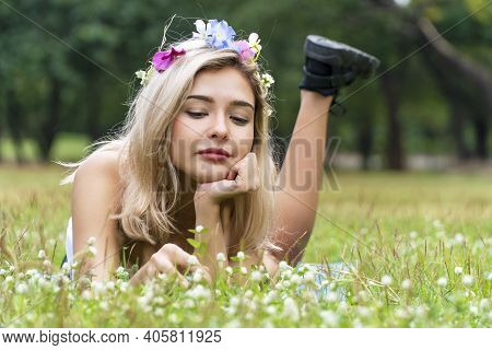 Allergy Free Concept. Charming Young Woman Lying Relaxed On The Meadow Green Grass With Wild Flowers