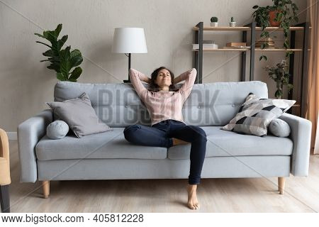 Peaceful Happy Young Woman Relaxing On Comfortable Sofa.