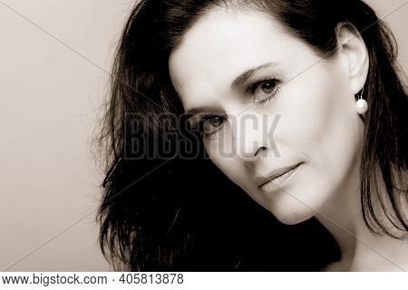 Portrait Of A Mature Brunette Woman Sitting And Contemplates Realities Of Life