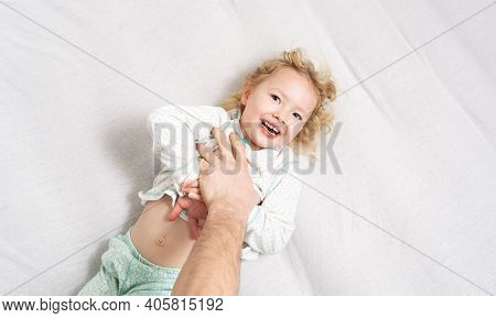 Family Time: A Little Girl Lies On The Bed And Laughs Cheerfully Because Of The Tickling Of Her Fath