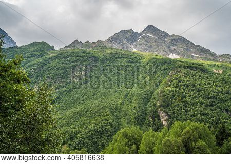 Mountain Ridge Covered With Forest Under Blue Sky. Picturesque Scenery Of Mountain Slopes And Peaks