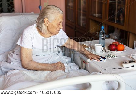 Elderly Sick Caucasian Woman Measures Pulse Sitting In Bed At Home. Nearby On Table Fruits, Water, C