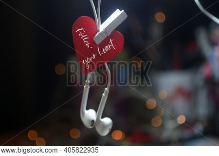 Inspirational Quote - Follow Your Heart. With Red Heart Hanging On White Earphone On Dark Bokeh Ligh