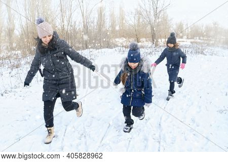 family plays and sleigh rides in winter outdoor, mother and children having fun on snowy winter