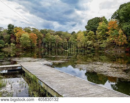Tomlinson Run State Park In West Virginia In The Fall With A Boat Dock In The Foreground And Colorfu