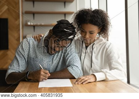 Focused Young Black Couple Signing Prenuptial Agreement In Lawyer Office