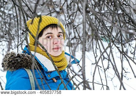 Young Woman In Bright Winter Hat And Jacket Among Branches Of Trees In Winter Park. Looking Into Cam