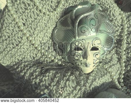Carnival Mask On A Knitted Background With Beads And Sparkles. Carnival Festival Costume Element. Pa