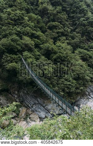 Narrow Walking Bridge Crossing Valley Into A Lush Green Forest In Taroko National Park In Hualien, T