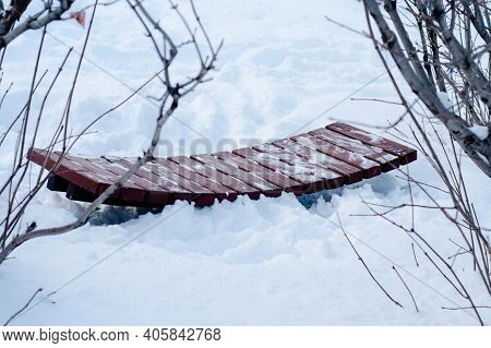 Concave Wooden Bench Made Of Narrow Planks In  Middle Of High Snowdrifts.  Bench For Reconciliation.