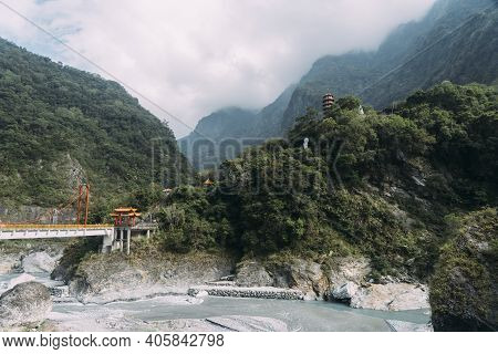 Wide View Of Xiangde Temple From Valley Below With River And Sharp Cliffs Behind.