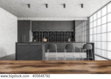 Wooden Desk Foreground And Blurred Background Of Black And Marble Minimalist Kitchen, Front View. Cu