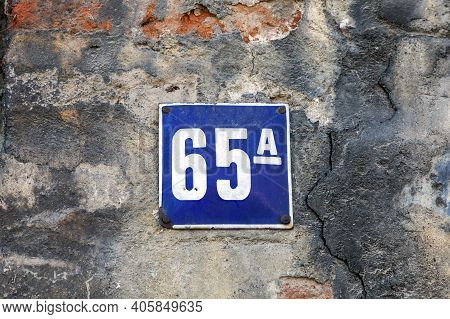 Number 65, The Number Of Houses, Apartments, Streets. The White Number On A Blue Metal Plate, House