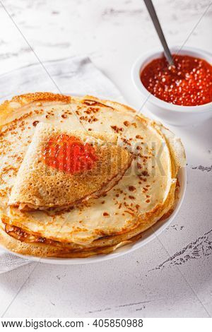 Traditional Russian Crepes Blini Stacked In A Plate With Red Caviar On Light Background. Maslenitsa