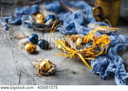 Colored Yellow And Blue Easter Quail Eggs In Small Nests. Quail Eggs For Catholic And Orthodox Easte