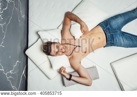 Man Lying On A White Pillow And A Mattress On A Gray Background. Concept Of Comfortable Sleep. Ortho
