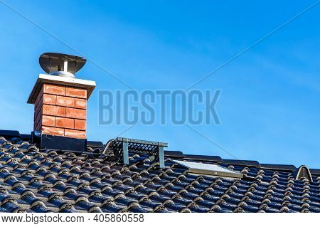 New Black Tiled Roof With Chimney. New Roof Of A Detached House With Chimney Against The Sky. Exteri