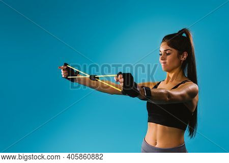 A Sporty Girl In A Black Top Stretches An Expander For Her Arms And Pectoral Muscles In Front Of Her