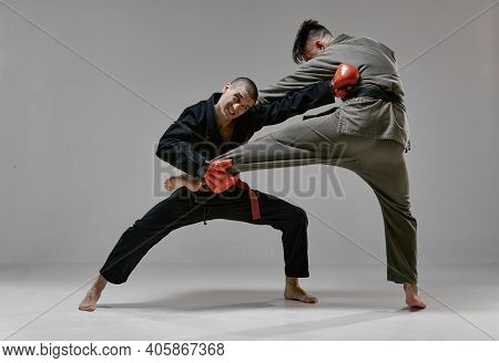 Fighting Guys During Mixed Fight Workout On Gray Studio Background. Athletic Males In Kimono And Box