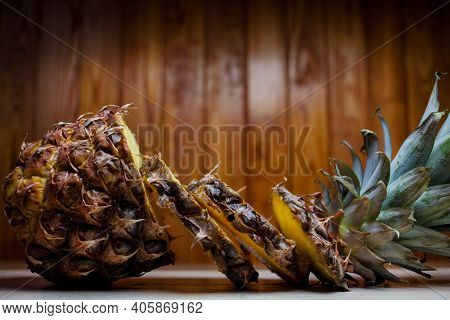 Sliced Pineapple On A Wooden Background. Ripe Pineapple On Brown Wooden Background. Pineapple And Pi