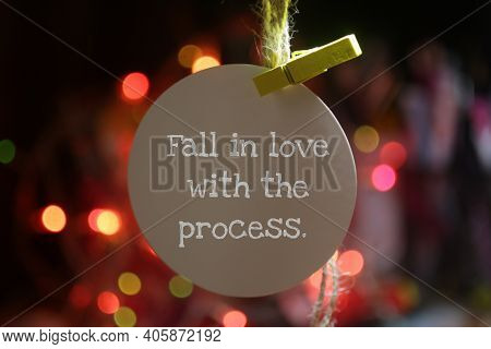 Fall In Love With The Process. A Note Reminder On White Tag Label Paper Hanging On Colorful Bokeh Li