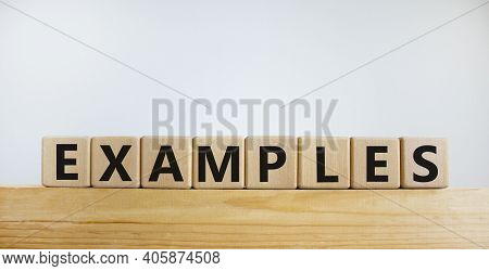 Examples Symbol. Concept Word 'examples' On Wooden Cubes On A Beautiful Wooden Table. White Backgrou