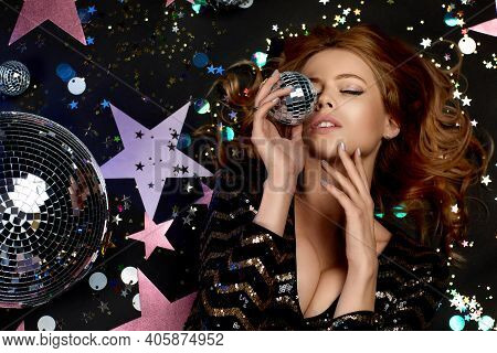Glamour Model Posing On The Floor. Sexy Blonde Woman In A Black Sequins Dress For Party Holding Mirr