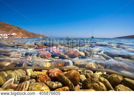 Closeup Photo of a Beautiful Pebbly Sea Bottom under Clear Water. View on Sailing Boats Standing in the Distance. Summer Vacation on the Beach Resort.