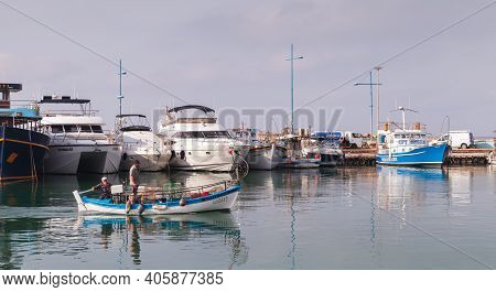 Ayia Napa, Cyprus - June 16, 2018: Fishermen On Wooden Boat Enter Agia Napa Marina In Morning
