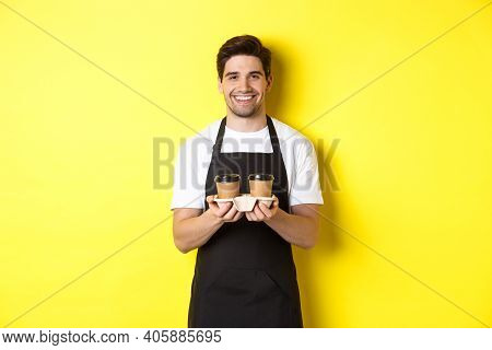 Handsome Male Barista Serving Takeaway Coffee And Smiling, Bringing Order, Standing In Black Apron A
