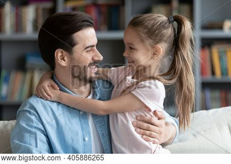 Affectionate Caring Young Smiling Father Cuddling Little Daughter.