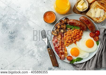 Full English Breakfast On A Plate With Fried Eggs, Sausages, Bacon, Beans, Toasts And Coffee On Ligh