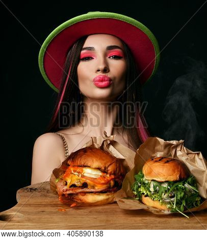 Beautiful Woman Hold Two Craft Big Burger Sandwiches With Hungry Mouth And Steam Smoke In Green Hat