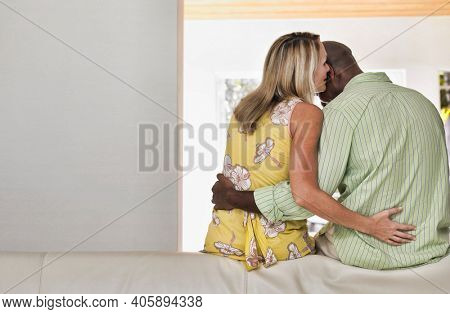 Rear view of a multiethnic couple showing affection in bed