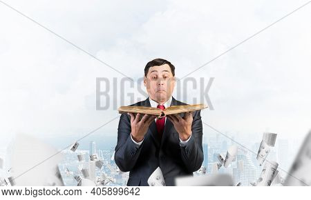 Surprised Businessman Holding Open Book. Startled Man In Business Suit Standing On Downtown Backgrou