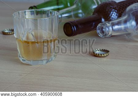 A Glass Of Beer, Empty Bottles And Corks On The Table. Alcohol Addiction Is A Concept. A Social Prob