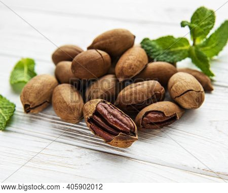 Pecan Nuts On A Old White Wooden Table