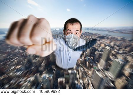 Masked businessman hero flying over a city, covid coronavirus prevention concept