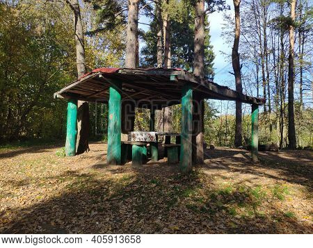 A Wooden Arbor In The Forest. A Cozy Place For A Family Holiday In Nature