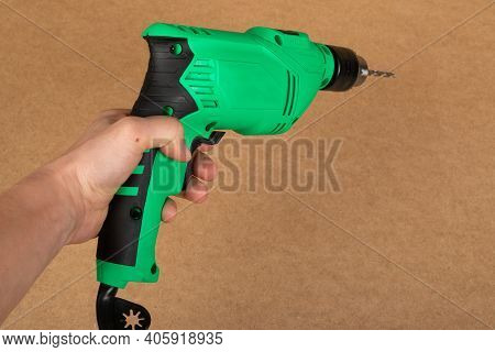 Picture Of A Green Jig Sawand A Drill On A Wooden Background
