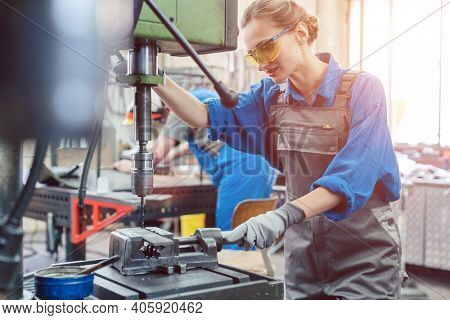 Metal worker woman operating drilling machine concentrating on her job