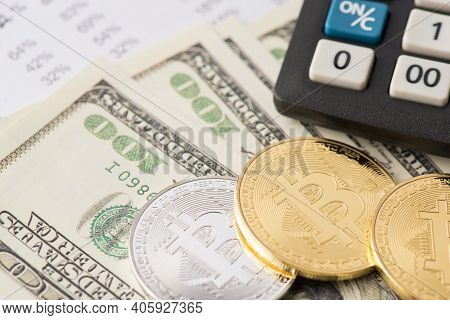 Close Up Photo Of Golden And Silver Bitcoin Laying On Stack Of American Bills Banknotes Near Calcula