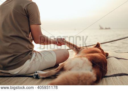 A Man Hold One Hand  With A Dog Pet Near The Sea Sunset. Travel, Vocation, Holiday Concept.