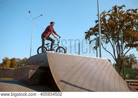 Bmx biker doing trick,teenager in skatepark